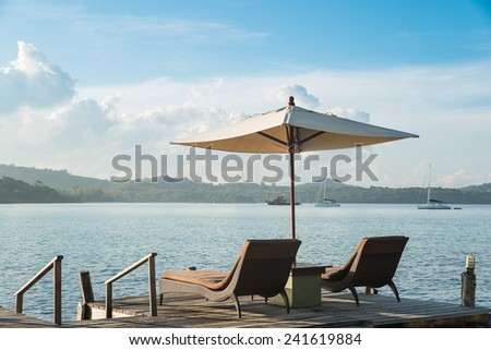 Two chairs beach and umbrella on wooden desk against blue sky. Summer travel in Phuket ,Thailand. - stock photo