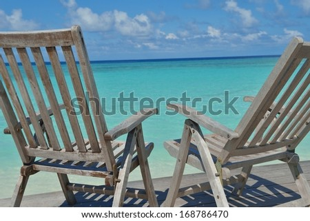 Two chairs beds in forest  on tropical beach with blue ocean in background - stock photo