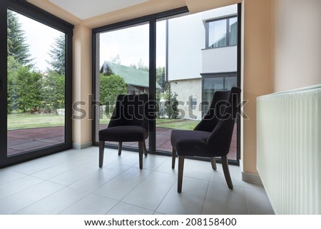Two chairs in glazed terrace with a view to a garden - stock photo