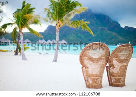 Two chairs on a beautiful beach of Bora Bora at evening - stock photo