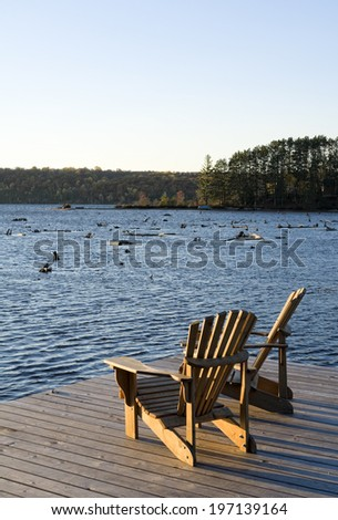 Two chairs on a dock overlooking a lake. - stock photo