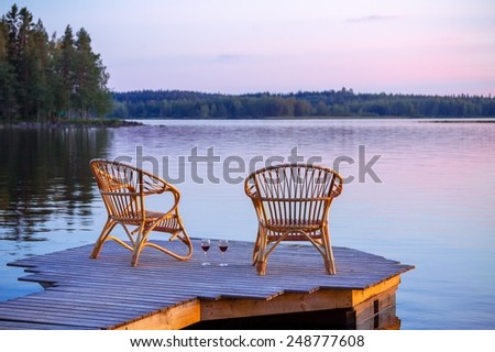 Two chairs on dock with glasses of wine - stock photo