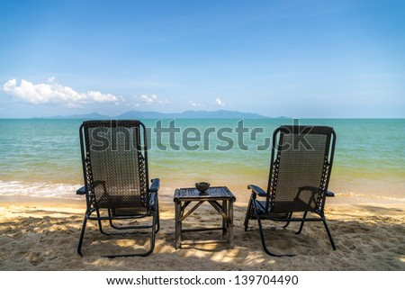 Two chairs on the beach in the shadow of a palm trees - stock photo