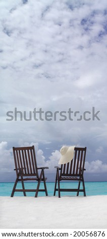 two chairs on the beach with hat