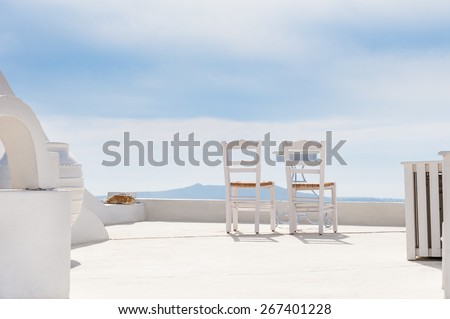 Two chairs on the terrace. White architecture on Santorini island, Greece. Summer holidays - stock photo