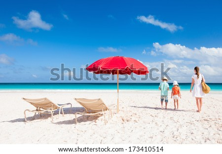 Two chairs under umbrella on a beautiful tropical beach with family walking nearby