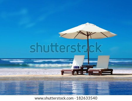 Two Chairs with White Umbrella near the Beach - stock photo