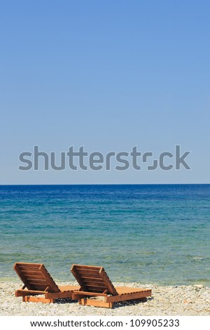 Two chaise lounges standing in the beach near the sea