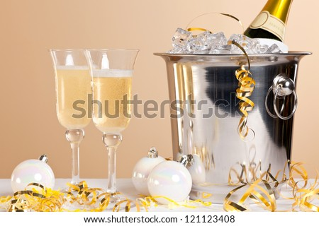 Two Champagne flutes and a bottle in an ice bucket - stock photo