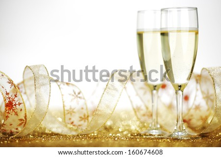 Two champagne flutes and decoration on gold shiny background - stock photo