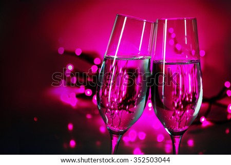 Two champagne flutes clink glasses on New Year's party, purple background with blurred lights and copy space - stock photo