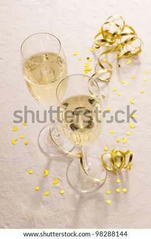 Two champagne flutes on a tablecloth with gold ribbon and ornaments. - stock photo