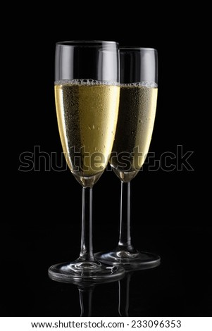 Two champagne flutes on black