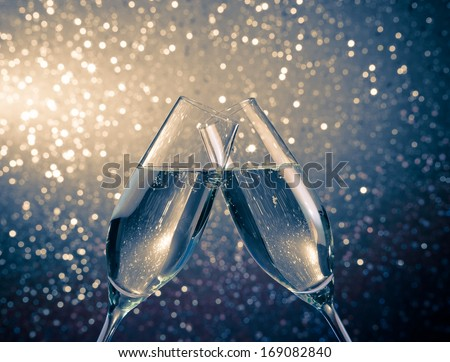 two champagne flutes with golden bubbles make cheers on blue light bokeh background with space for text - stock photo