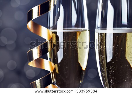 Two champagne glasses and curly ribbons on dark background - stock photo