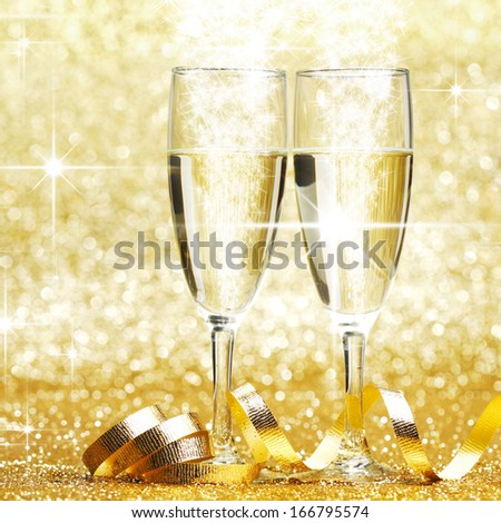 Two champagne glasses and decoration on golden stars background