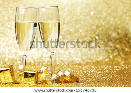 Two champagne glasses, gifts and decoration on golden background