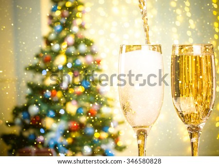 Two Champagne Glasses On Defocused Background Living Room With Christmas Tree and glitter lights - stock photo
