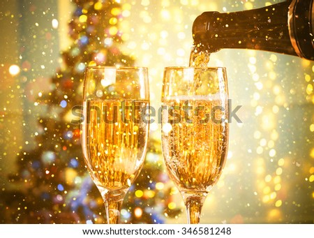 Two Champagne Glasses On Defocused Background Living Room With Christmas Tree and glitter lights