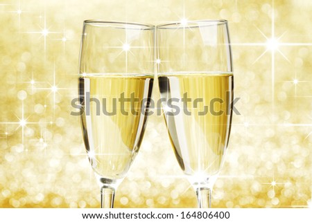 Two champagne glasses on golden shiny stars background