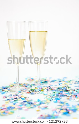 Two champagne glasses with alcohol and colored confetti decoration isolated on white background - stock photo