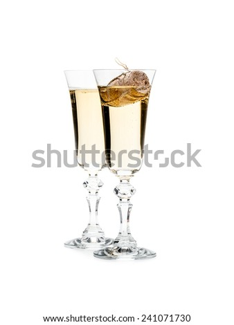Two champagne glasses with champagne cork floating in one glass shot on white - stock photo