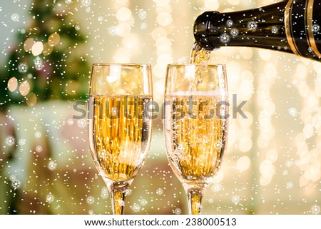 Two Champagne Glasses With Snow and Stars On Defocused Background Living Room With Christmas Tree