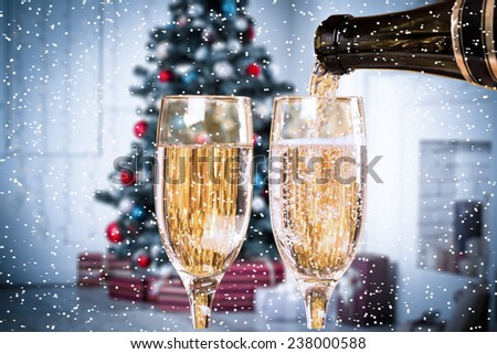 Two Champagne Glasses With Snow On Defocused Background Living Room With Christmas Tree. Blue toned