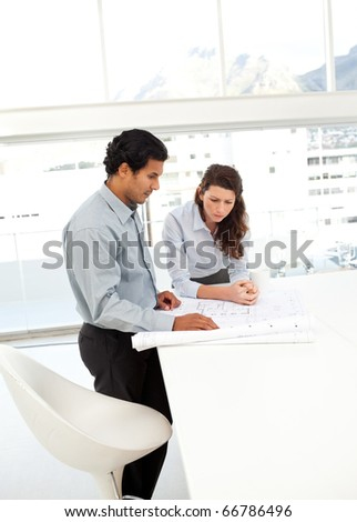 Two charismatic architects working on a new projects standing in the office - stock photo
