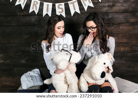 Two charming girls playing with Christmas toys - stock photo