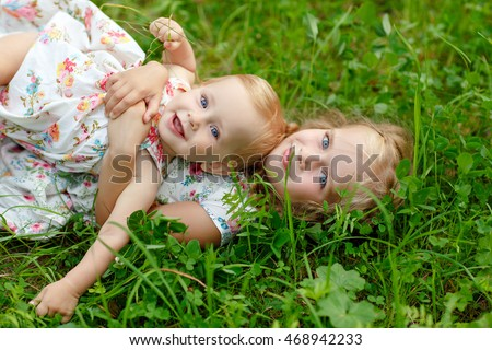 Two charming sisters blonde girl hugging and laughing, lying on the grass in the summer
