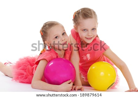 Two charming sisters love to play ball.Isolated on white background. - stock photo