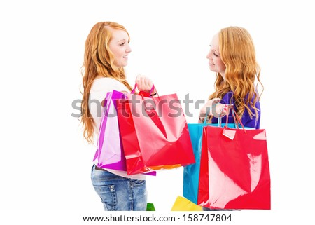 two chatting redhead women with shopping bags on white background - stock photo