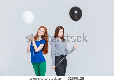Two cheerful and upset young women holding black and white balloons - stock photo