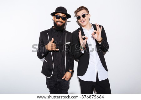 Two cheerful attractive young men standing and showing ok gesture over white background - stock photo
