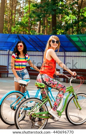 Two cheerful beautiful funny hipster girls, teenagers, best friends, ride bicycles in the park, laughing, crying, dressed in bright T-shirts, denim shorts, leggings, sunglasses, a healthy lifestyle - stock photo