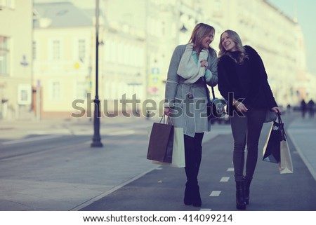 two cheerful blonde for a walk in the city - stock photo