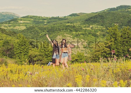 Two cheerful boho hippie style sisters in nature on sunny summer day. Young female friends having fun outdoors. Mild retouch and filter, natural light. - stock photo