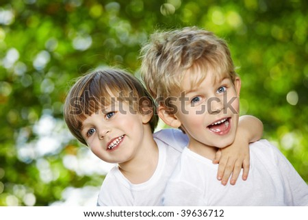 Two cheerful boys embrace in a summer garden