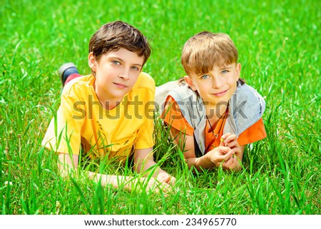 Two cheerful boys lying on the grass in the park. Summer. - stock photo
