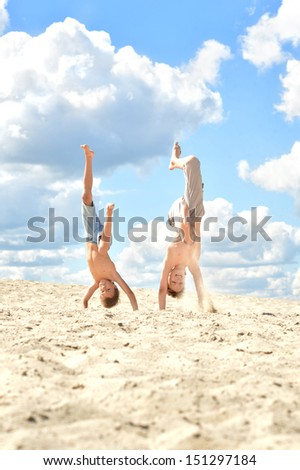 Two cheerful boys standing on their hands on a sand - stock photo