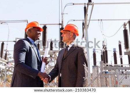 two cheerful businessman handshaking in electric substation - stock photo