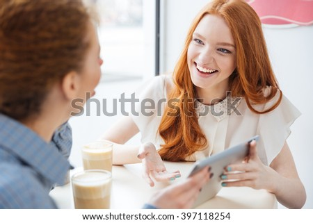 Two cheerful charming young woman smiling and using tablet in cafe - stock photo