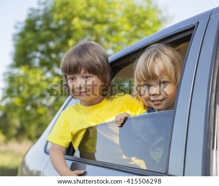 two cheerful child sitting in the car on nature - stock photo