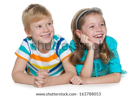 Two cheerful children are lying together and looking aside on the white background