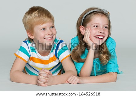 Two cheerful children are lying together on the floor
