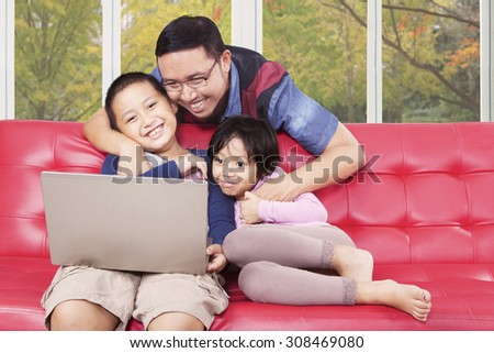 Two cheerful children using laptop computer for watching movie with their father at home - stock photo