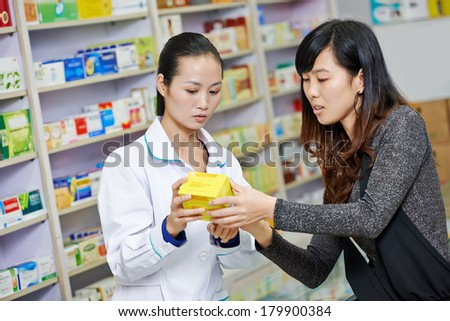 Two cheerful chinese pharmacist chemist woman standing in china pharmacy drugstore - stock photo