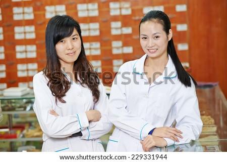 Two cheerful chinese pharmacist chemist woman standing in china pharmacy drugstore - stock photo