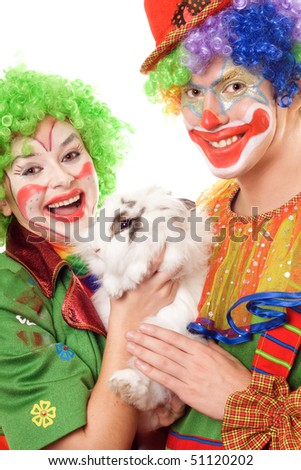 Two cheerful clown with a white rabbit. Isolated - stock photo
